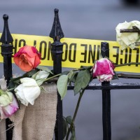 Roses and crime scene tape are laced through the wrought iron fence at the memorial on the sidewalk in front of the Emanuel AME Church, Saturday, June 20, 2015  in Charleston, S.C. People started visiting the site well before sunrise four days after a gunman shot and killed nine people during a Bible study session at the church on Wednesday. (AP Photo/Stephen B. Morton)