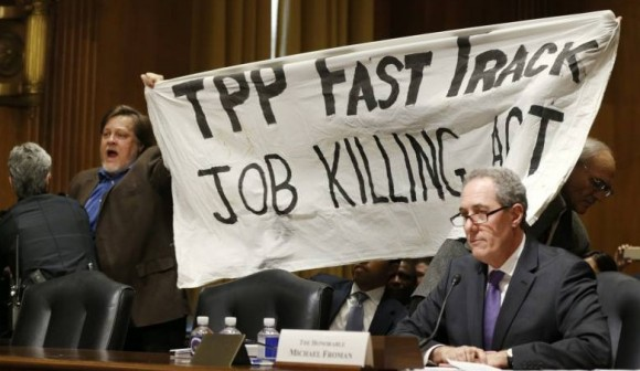 TPP-Protest-Froman-miffed-as-KZ-and-Dick-Ochs-hold-banner-behind-him.-Source-Reuters.-e1422650179158