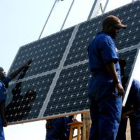 Training workers to install solar panels at health clinics in rw